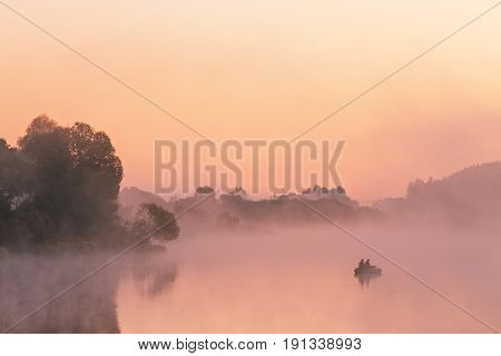 Two Anglers On A Boat Enjoys Fishing On A Beautiful Morning.