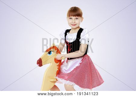 A sweet little blonde with long hair braided in a bun and a short bangs on her head. In a beautiful dress with a white apron.She rocks on a toy wooden horse.