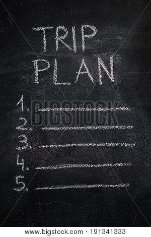 Trip plan list written with white chalk on blackboard. To do list, trip, vacation concept