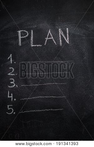 Plan list written with white chalk on blackboard. To do list concept