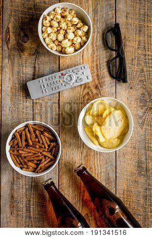 home party with TV watching, snacks, pop corn, chips and bread crumbs and beer on wooden background top view