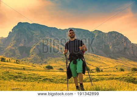 Young man with nordic sticks hiking at dusk in Apuseni Mountains in TransylvaniaRomania.