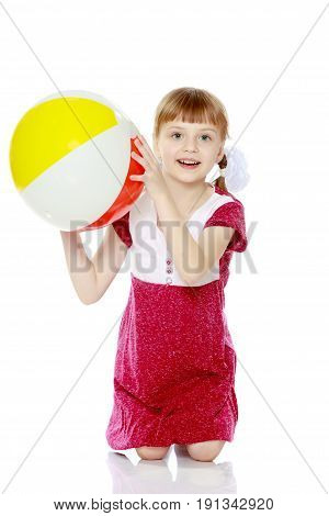 A little fair-haired girl with pigtails and a short bangs, in a short, red summer dress.She plays with a large striped inflatable ball.