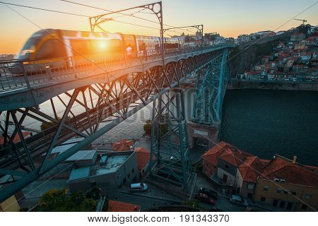 PORTO, PORTUGAL - JUNE 15, 2017: Train of Porto Metro on Dom Luis iron Bridge at sunset time. The network has 6 lines and reaches seven municipalities within the metropolitan Porto area.