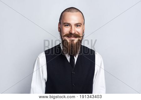 Happiness. Handsome businessman with beard and handlebar mustache looking at camera with toothy smiley face. studio shot on gray background.