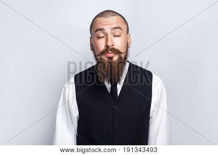 Kissing. Handsome businessman with beard and handlebar mustache closed eyes and kissing. studio shot on gray background.