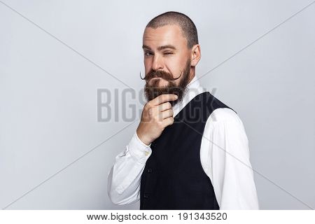 thoughtful Handsome businessman with beard and handlebar mustache looking at camera and thinking. studio shot on gray background.