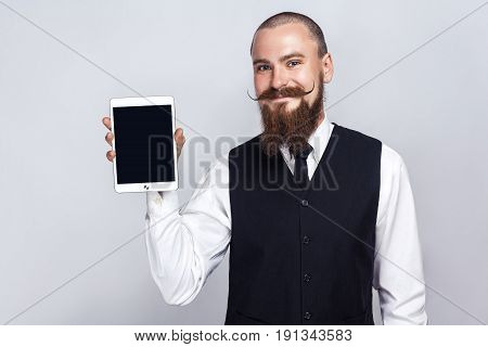 Handsome businessman with beard and handlebar mustache holding digital tablet and looking at camera and showing screen with smiley face. studio shot on gray background.