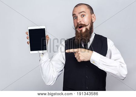 Handsome businessman with beard and handlebar mustache holding digital tablet and looking at camera and showing screen with finger and surprised. studio shot on gray background.