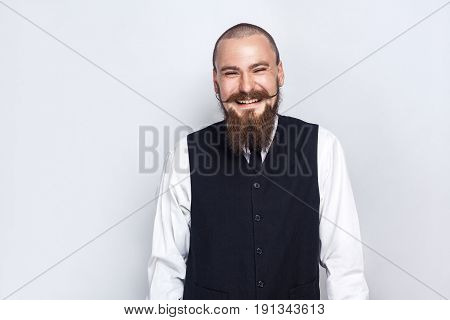 laughing. Handsome businessman with beard and handlebar mustache looking at camera with laugh face. studio shot on gray background.