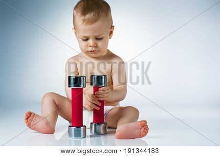 Eight month baby sitting and playing with dumbbells on white background