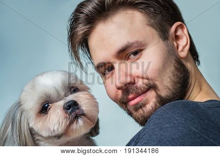 Young man with shih tzu dog portrait. Love and care concept.