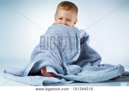 Eight month baby after washing sitting in big soft towel and smiling on white background