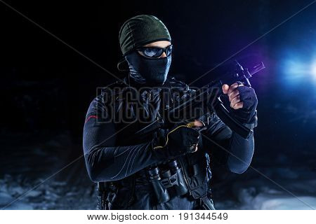 Strong man military special forces standing with gun on snow at night