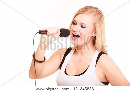 Karaoke music singer concept. Blonde woman singing to microphone performance of young star studio shot isolated