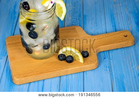 lemonade drink in mason jar with blueberries and polka dot straw on wooden cutting board