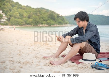 Young Asian man using smartphone on tropical beach digital nomad lifestyle or freelance occupation concepts