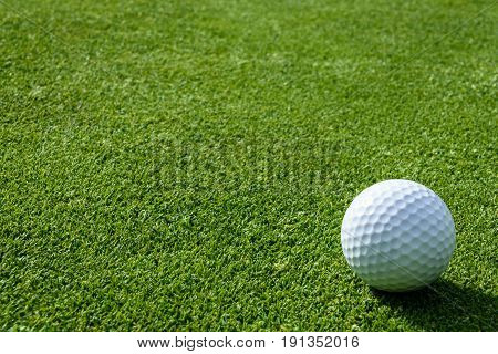 Side view of golf ball on a putting green