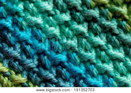Close-up of blue, teal, and green crocheted yarn rows