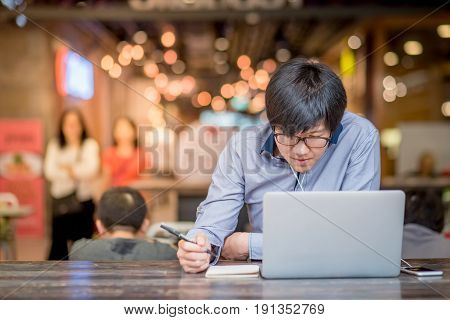 Young Asian Business man dressed in casual style contact with customer when working in cafe. Digital nomad lifestyle in public working space.