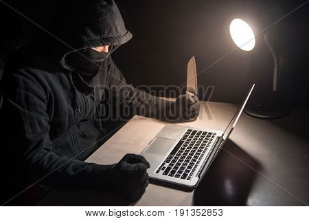 Male hacker threading computer laptop with knife showing on screen with ransomware warning internet security system concept