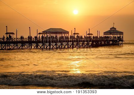 The romantic sunset time at pier of Huanchaco town neat Trujillo Peru