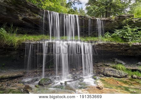 Water splashes over the two-tiered plunge of the waterfall at Oglebay Park in Wheeling West Virginia.
