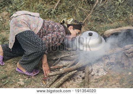 Lasak- Iranian village Muslim women in traditional clothing kneeled and blow out on fire in outdoor area preparation food