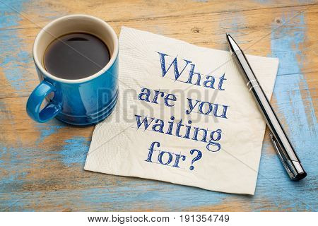 What are you waiting for question - handwriting on a napkin with a cup of espresso coffee