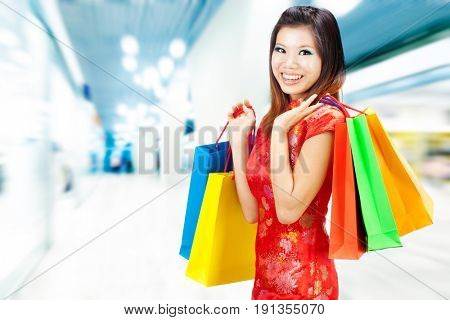 Oriental woman in red Traditional Chinese Cheongsam with shopping bag, standing inside mall.