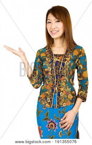 Southeast Asian girl wearing batik kebaya holding hand showing something, standing isolated on white background.