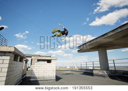 Man flips on the roof of high-rise building. Parkour. Active lifestyle. Roofer