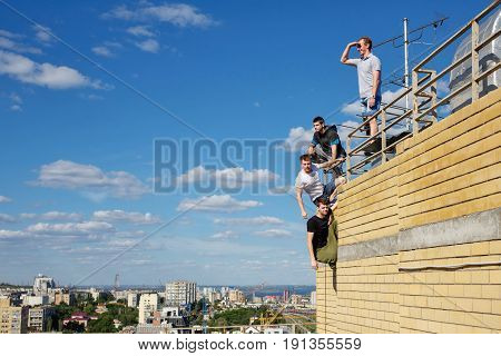 A group of roofer climbs the stairs to the roof. Active way of life in urban space. Courage and adrenaline.