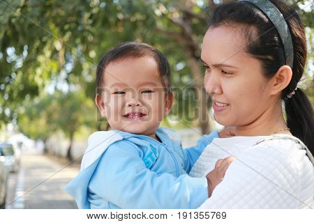 Asian boy is smiling happily in his mother's armsconcept of love and health of the baby.