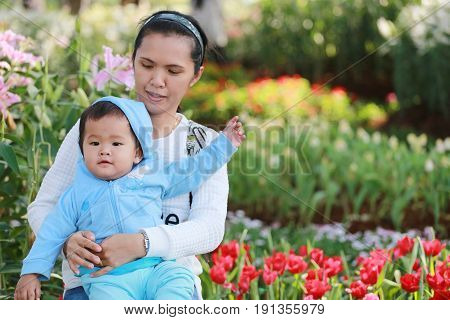 Asian boy is happily in his mother's arms in flower gardenconcept of love and health of the baby.