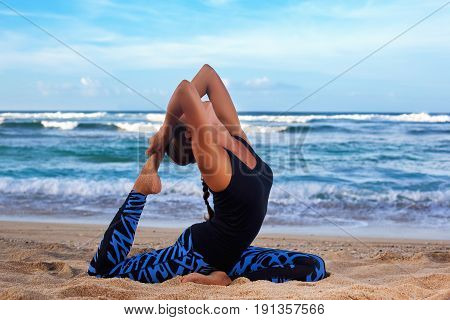 Young Woman Practicing Yoga On The Beach At Sunrise