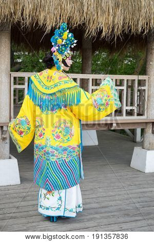 Beautiful Chinese Girl In Traditional Chinese Dress With Long Sleeves And Hat With Pompons Standing