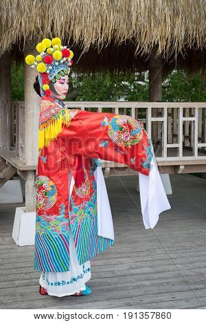 Beautiful Chinese Girl In Traditional Chinese Dress With Long Sleeves And Hat Standing Outdoor Profi