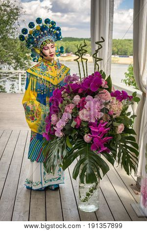 beautiful chinese girl in traditional chinese dress and pompon hat standing near the big peony and orchid bouquet