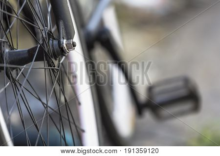 Close-up shot of front wheel of a bicycle with bokeh background.