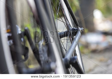 Close-up shot of rear wheel of a bicycle with bokeh background.