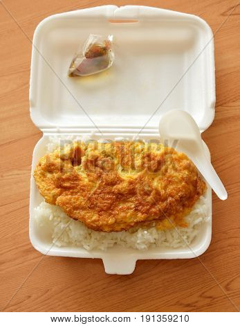 fried egg on rice in foam box with plastic spoon ready for eat