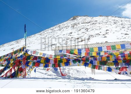 Prayer flags is a colorful rectangular cloth often found strung along mountain ridges and peaks high in the Himalayas in Chang la pass road Leh India