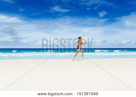 Photo of the youn woman jogging on the beach