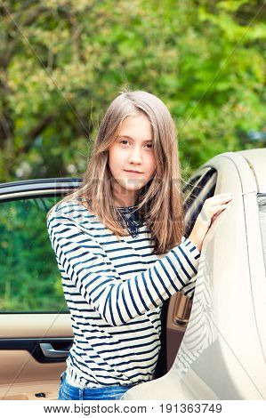 Girl standing close to the car looking at camera. Summertime outdoors.