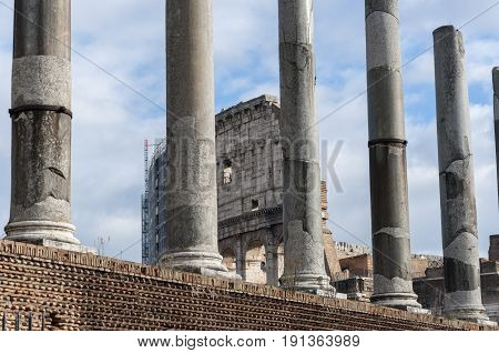 Views of Colosseum behind a line of columns from the Roman Forum