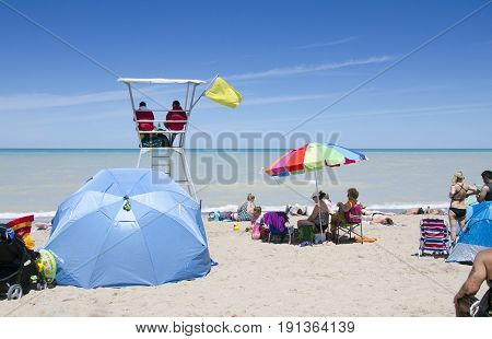 Grand Bend Ontario, Canada - July 02, 2016: Two Lifeguards Sitting In Their Chair And Watching The B