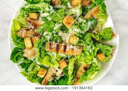 A closeup photo of a plate of chicken Caesar salad, shot from above on a white marble background with a place for text