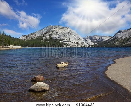 Flat shore of picturesque shallow lake at Tioga Pass in Yosemite Park