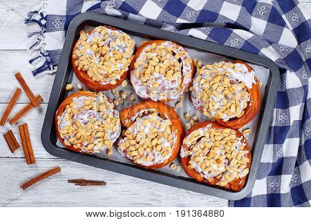 Cinnamon Rolls With Peanuts On Baking Sheet